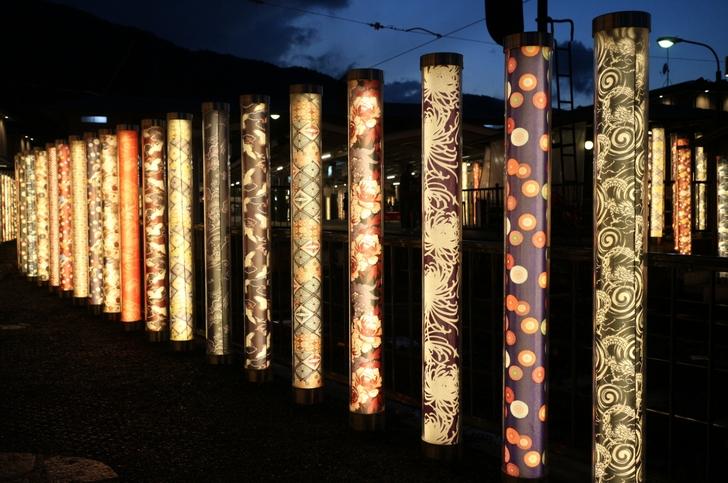 京友禅の着物を使ったライティングされたポールが大量に並ぶ嵐山駅