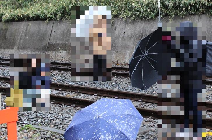 傘を線路内に置いて、1歳前後の子供と撮影する外国人観光客