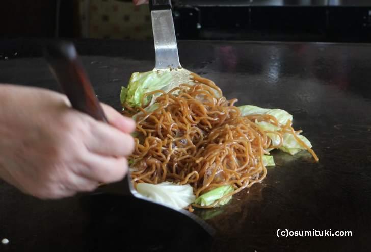 野菜がしんなりするまで炒め、麺は短めにカットされます