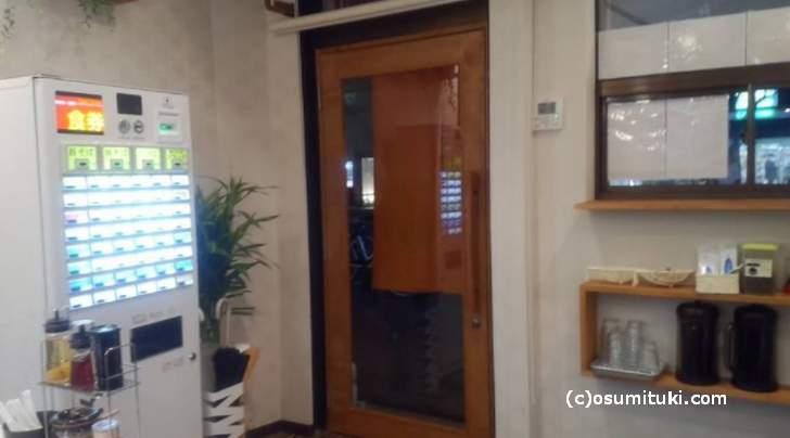 内装は白が基調で、入口に券売機があります