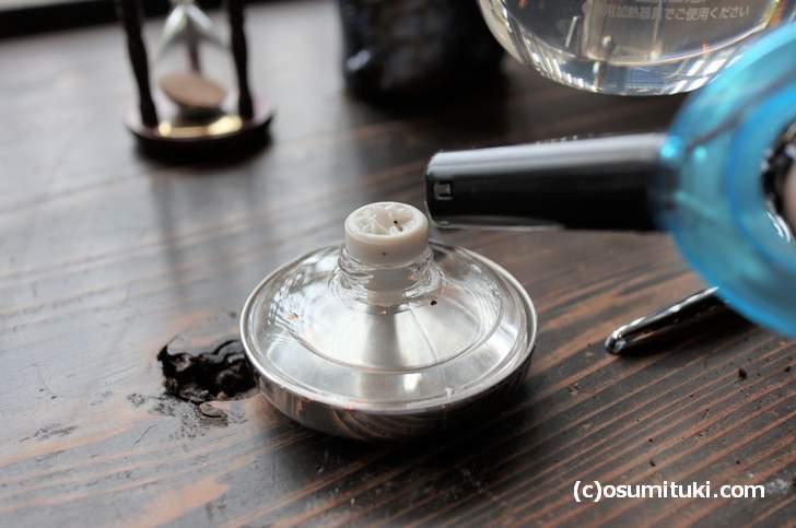コーヒー豆はヘラで平坦にしてからランプでお湯を沸かす