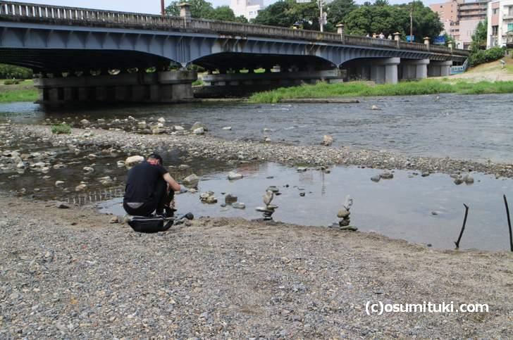 奇跡のバランスで石を積む人(京都・鴨川)