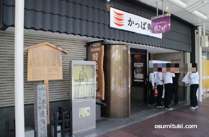 回転寿司の「かっぱ寿司」の前で校外学習する中高生(近江屋跡)