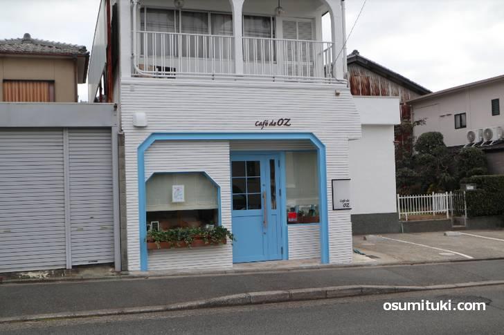 白い壁に水色のドアや窓枠が目立っています(Cafe de OZ)