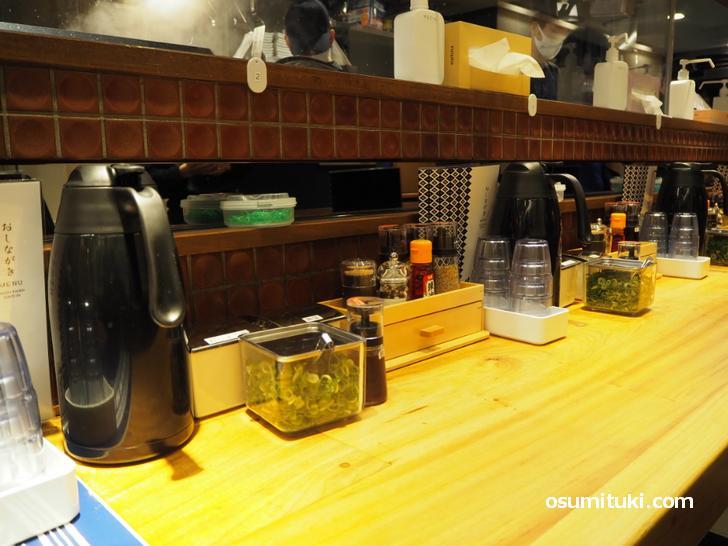 各席に「水・箸・輪ゴム・調味料・ネギ・紅ショウガ・高菜」がある