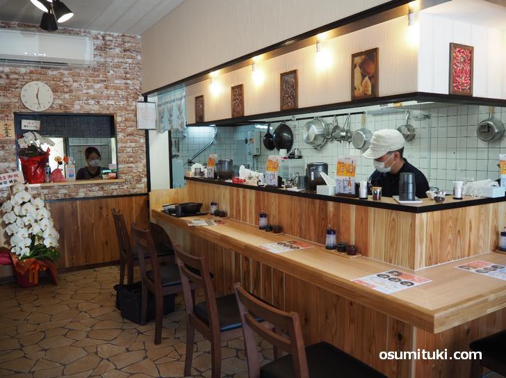 L字カウンターと厨房、テーブル席もある店内